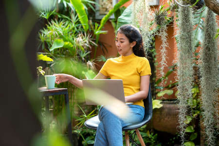 Young people work from home with laptop and drinking coffee in morning relax at home. Asia woman meeting conference connect online with office.  Business and Technology Concept