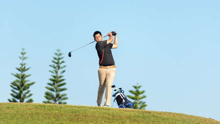 Golfer asia man approach on tee off for swing and hitting golf ball on slope green and looking fairway in course. Hobby playing game golf in holiday and vacations day on club golf.  Lifestyle sport concept