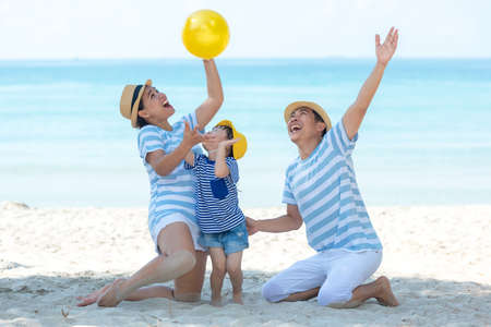 Asian happy family have fun and play yellow ball on the beach.  Family people tourism travel in summer and holiday  for leisure and destination. Travel and Family Concept Фото со стока