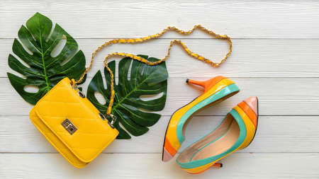 Fashion bag  woman accessories wood white background. Trendy fashion luxury yellow handbag design with monstera leave green. Lifestyle and Beauty Concept