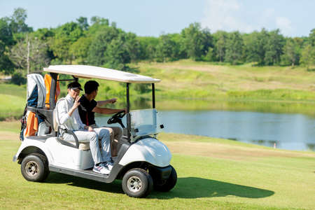 Group Golfer asian man and friend sitting on the car golf go to golf course shot continue game.  Hobby in holiday and vacations in sunny morning day on club golf. Lifestyle and Sport Concept Фото со стока