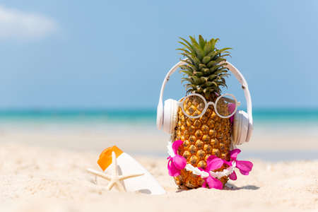 Summer in the party.  Hipster Pineapple Fashion in sunglass and listen music with sunblock and sandal on the sand beach beautiful blue sky background.  Creative art fruit for tropical style.   Fashion Summer Vacation Concept Фото со стока
