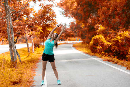 Healthy woman warming up before jogging run and relax stretching her arms and looking away in the road outdoor. Asian runner people workout fitness session, autumn nature park background. Healthy and Lifestyle Concept.