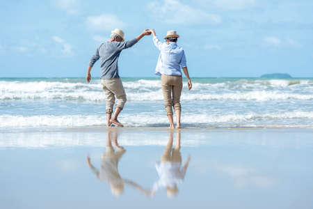 Retirement Travel. Asian Lifestyle senior couple dancing on the beach happy and relax time.  Tourism elderly family travel leisure and activity after retirement in vacations and summer.