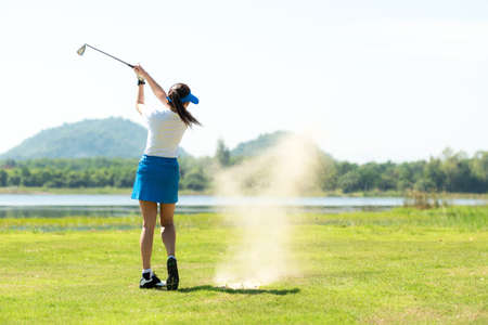 Golfer sport course golf ball fairway. People lifestyle woman playing game golf and hitting out of sand trap go on green grass. Asia female player game shot in summer. Healthy and Sport outdoor Foto de archivo