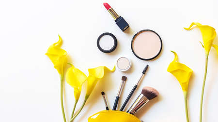 Makeup cosmetics tools and beauty cosmetics gift, products and facial cosmetics package lipstick with yellow flower on the white background, top view and copy space. Lifestyle Beauty Concept