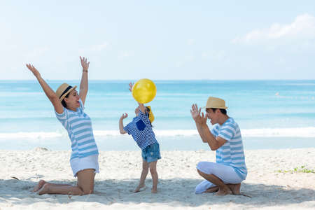 Asian happy family have fun and play yellow ball on the beach.  Family people tourism travel in summer and holiday  for leisure and destination. Travel and Family Concept Foto de archivo
