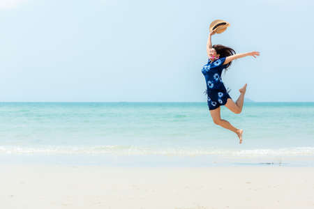 Summer vacations. Lifestyle woman relax and chill on beach background.  Asia happy young people jumping on the wave sea, summer trips walking enjoy tropical beach. Lifestyle and Travel Concept