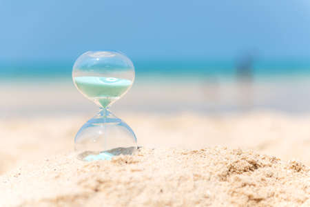 Hourglass summer and vacations time on a beach in the sand with blue sky and copy space. Lifestyle Concept. Foto de archivo