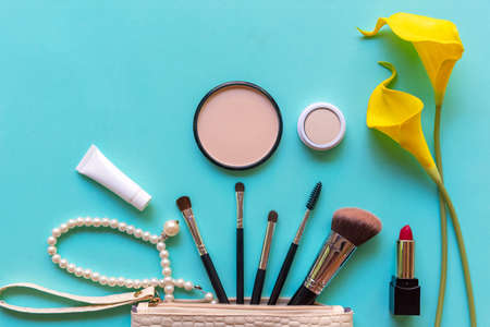 Makeup cosmetics tools background and beauty cosmetics, products and facial cosmetics package lipstick, eye shadow on the blue background. Lifestyle Fashion Concept Foto de archivo