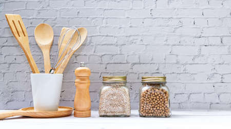 Kitchen tools and kitchenware utensil object with ingredients and mix nut on kitchen shelf wood white for healthy eat and health care life.  Wall white brick background, copy space for text