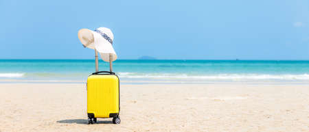 Summer traveling and tourism planning with yellow suitcase luggage with big hat fashion in the sand beach. Travel in the holiday, blue sky and beach background. Summer and Travel Concept, copy space for banner Foto de archivo
