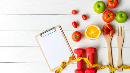 Planning for Diet Health eat and food.  Sport exercise equipment workout with fresh fruit and measuring tap, note pad for fitness style. Nutrition Healthy Lifestyle Concept, Top view and copy space Foto de archivo