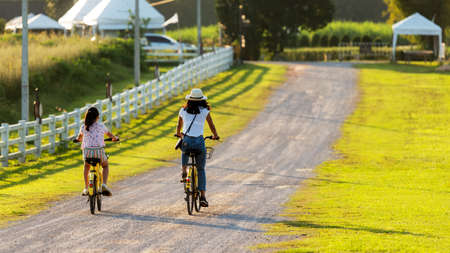 Family Happy.  Mother and daughter smiling happy outdoor with bicycling at the garden meadow in sunset.  Lifestyle Family Concept Foto de archivo