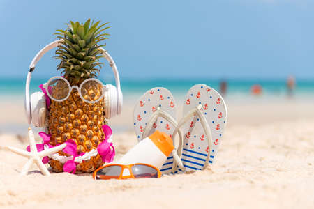 Summer in the party.  Hipster Pineapple Fashion in sunglass and listen music with sunblock and sandal on the sand beach beautiful blue sky background.  Creative art fruit for tropical style.   Fashion Summer Vacation Concept Foto de archivo
