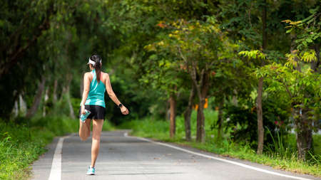 Healthy woman warming up before jogging run and relax stretching her arms and looking away in the road outdoor. Asian runner people workout fitness session, nature park background. Healthy and Lifestyle Concept
