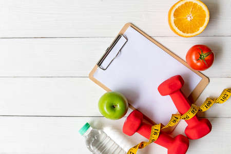 Planning for Diet Health eat and food.  Sport exercise equipment workout with fresh fruit, measuring tape, note pad for fitness style. Nutrition Healthy Lifestyle Concept, Top view and copy space