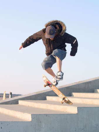 teenage guy: Young teenage guy doing a stunt with his skate board