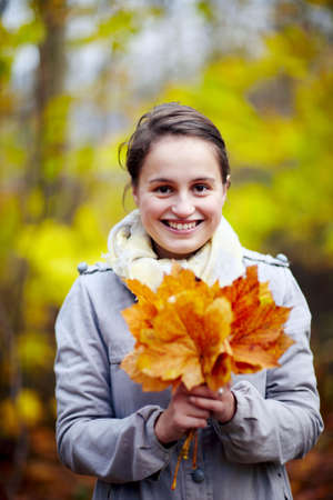 Cute young woman holding leaves in forest - autumn photo