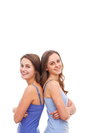 Two cute young women standing back to back on white