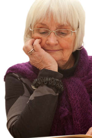 Thoughtful older woman reading a book with glasses photo