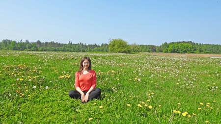 dandelion field: Young smiling woman on dandelion field. Spring 2016.