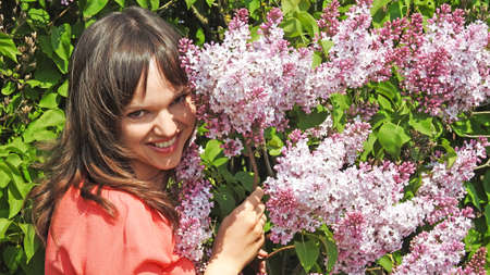 smilling: Young smilling woman with lilac. Spring 2016.