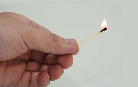 glow stick: Burning wooden match in a mans hand.