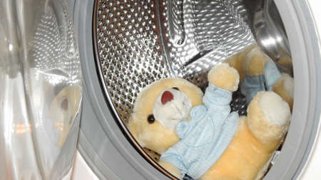 launderette: Yellow toy Bear located in washing machine. Stock Photo