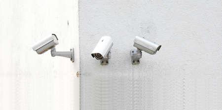 tilt: Three new surveillance cameras on a building wall Stock Photo