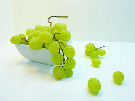 Fresh green grapes in plate isolated on white background Stock Photo