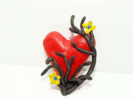 plasticine: Red heart made of plasticine. Plasticine abstraction on white background. Stock Photo