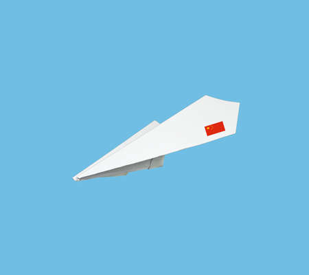 Plane made from paper with flag. Isolated on blue background. Stock Photo