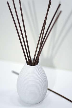 christmas perfume: Aromatic sticks for home in white ceramic vase. Isolated on white Stock Photo