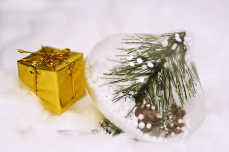 Macro photo of some Christmas objects. Yellow present with decorative cones in glass located on snow.