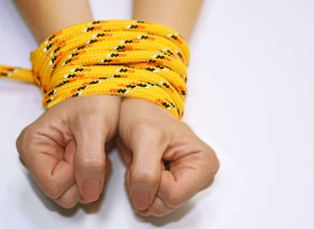 limited: Woman hands tied with rope. Stock Photo
