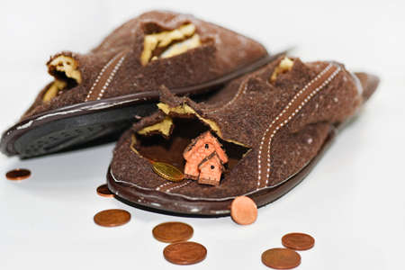 Leaky brown slippers. Abstract composition of poverty. Isolated on white background.