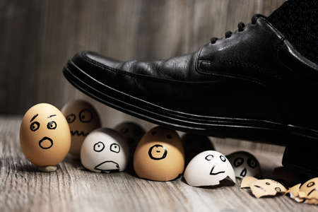 Abstract composition of business leadership. Broken eggs under mans shoes. Stock Photo