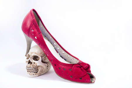 Abstract composition with woman red shoes and small skull.