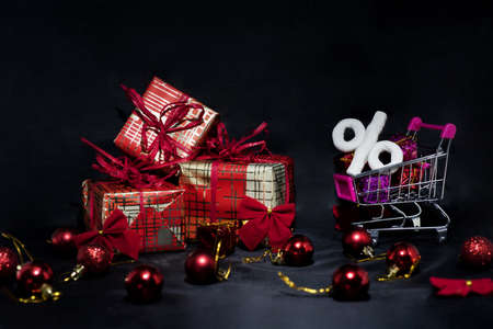 Black Friday abstract photo. Happy Merry Christmas. Shopping cart with decorative presents. Фото со стока