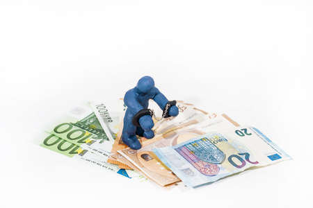 Abstract photo of financial scamming. Small figure made from Play Clay in handcuffs.