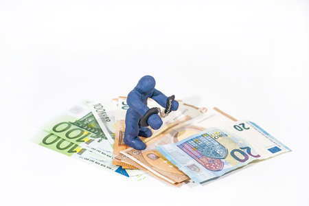 Financial scamming. Small figure made from Play Clay in handcuffs. Stock Photo