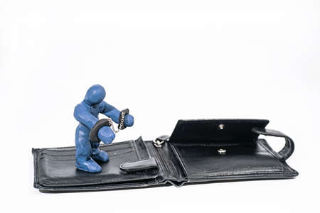 Abstract photo of theft and fraud. Small figure made from Play Clay with purse isolated on white background.