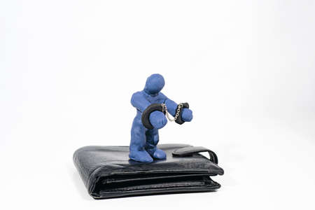 Theft and fraud. Small figure made from Play Clay with purse isolated on white background.