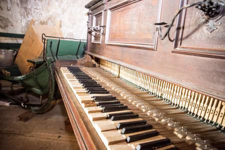 Old wooden broken piano. Abstract inside retro photo.