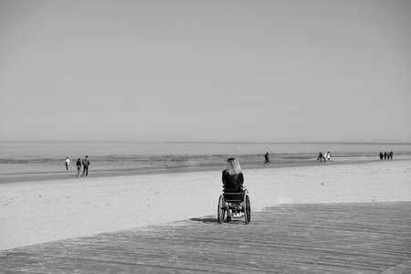 lonely disabled young woman on beach. Sunny summer day. Stockfoto