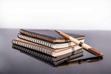 Folders,paper and pen on black glass table. Zdjęcie Seryjne