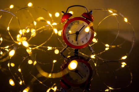 Alarm Clock And Christmas Lights Against Blurred Background. Winter Night Zdjęcie Seryjne - 133358413