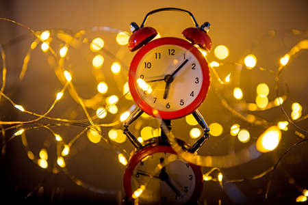 Alarm Clock And Christmas Lights Against Blurred Background. Winter Night