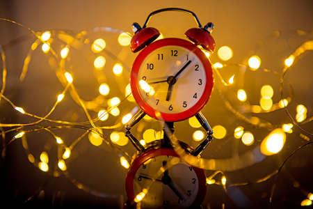 Alarm Clock And Christmas Lights Against Blurred Background. Winter Night Zdjęcie Seryjne - 133358416